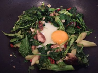 Kate's stir-fried in coconut oil leafy vegetables with egg on thrivelowcarb.com